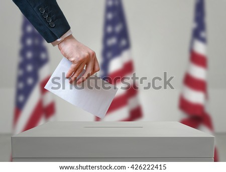 Election in United States of America. Voter holds envelope in hand above vote ballot. USA flags in background. Democracy concept. - stock photo