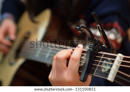 Electric Acoustic guitar neck with a capo - stock photo