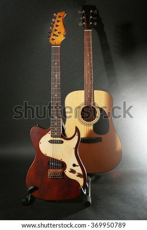 Electric and acoustic guitars on dark grey background - stock photo