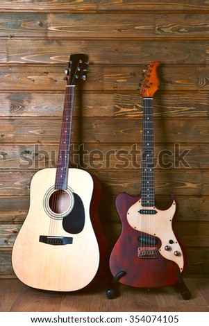 Electric and acoustic guitars on wooden background - stock photo