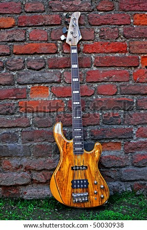 Electric Bass Guitar against the Wall - stock photo