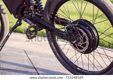 Electric bike motor wheel close up with pedal and rear shock absorber. Ebike bicycle environmentally friendly eco e-mountainbike transport. Healthy lifestyle