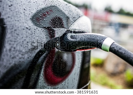 Electric Black Car charging at an Electric petrol charging station - E-Mobility - stock photo