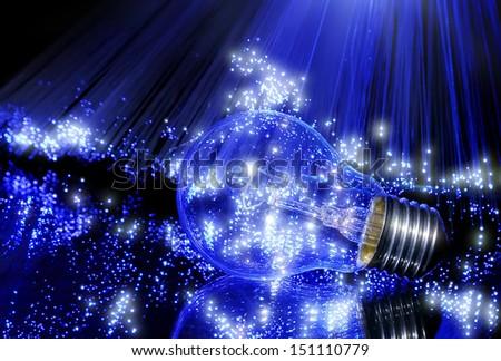 Electric bulb in light rays of fiber optics - stock photo