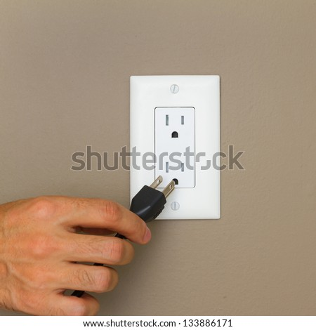 Electric cable with hand and Electrical Outlet on the Wall. Power 110v - stock photo