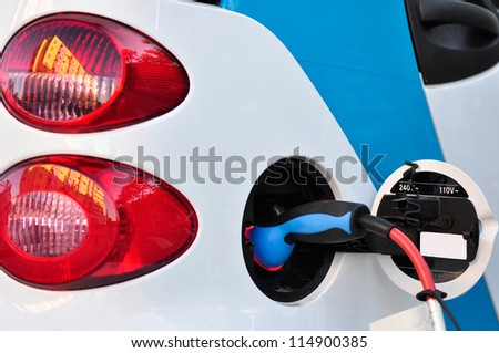 Electric car being recharged on a service station - stock photo