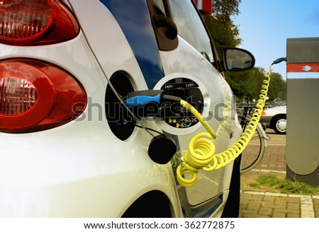 Electric car pluged on the cable power. - stock photo
