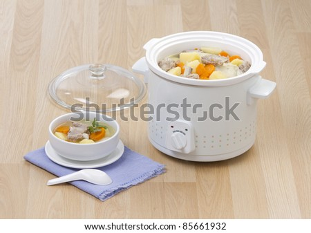 Electric casserole or stew  pot on the wooden kitchen table