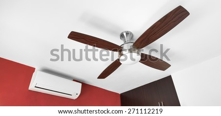 Electric ceiling fan and split-system air conditioner at the room  - stock photo