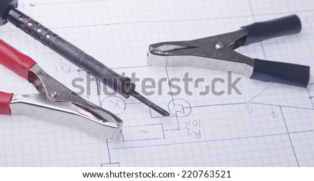 Electric clamps and a soldering iron on a background of the electric scheme  - stock photo