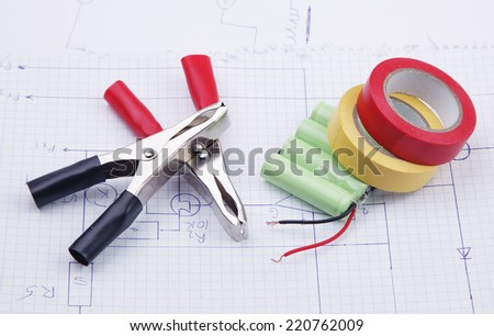 Electric clamps and battery on a background of the electric scheme - stock photo