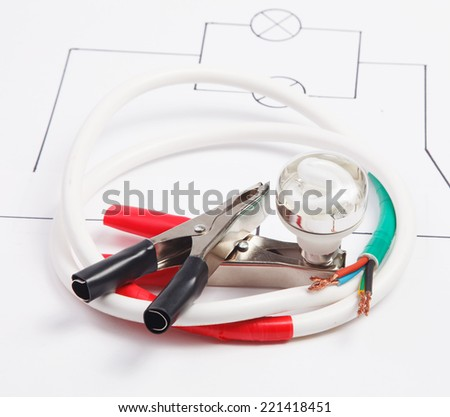 Electric clamps and electric cable on a background of the electric scheme  - stock photo