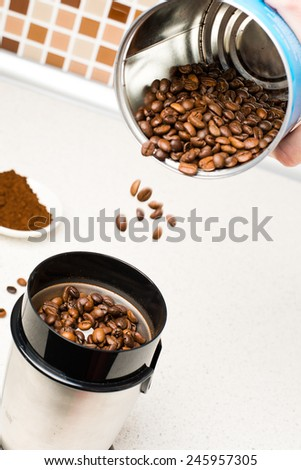 Electric coffee-mill machine with roasted coffee beans on the kitchen table - stock photo