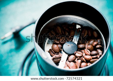 Electric coffee-mill machine with roasted coffee beans with open top on the kitchen table with green tabletop - stock photo