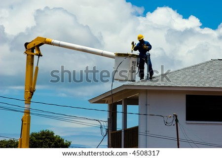Electric Company repairman on top of a house hooking up the power cables - stock photo