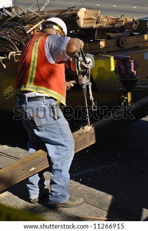 Electric company worker drills a hole in a cross beam for a new power pole