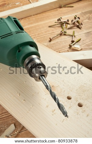 Electric drill on wooden board - stock photo