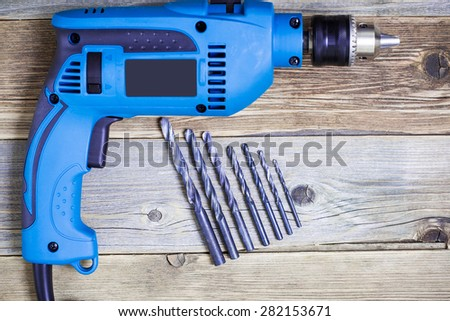 electric drill with a set of drill bits on the old workbench - stock photo