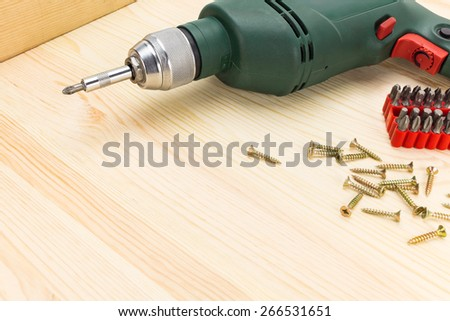 Electric drill with screwdrivers and screws on a wooden background - stock photo