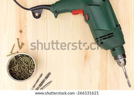 Electric drill with screws on wooden background - stock photo