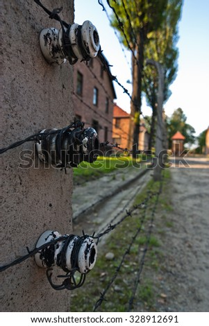 Electric fence and buildings in former Nazi concentration camp Auschwitz I, Poland - stock photo
