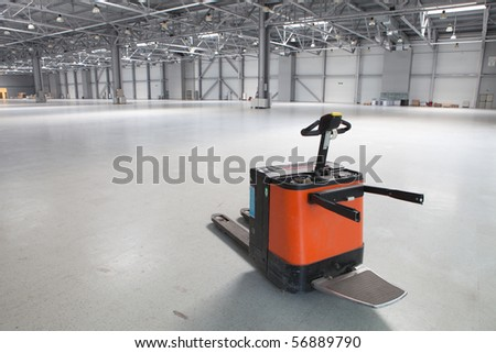 Electric forklift in large modern storehouse with some goods - stock photo