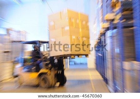Electric forklift in warehouse loading cardboard boxes. Intentional optical zooming blur - stock photo