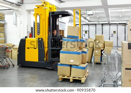 Electric forklift stacker in warehouse with boxes - stock photo