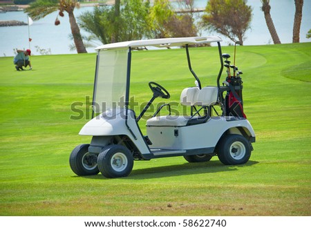 Electric golf buggy parked on the fairway of a golf course - stock photo