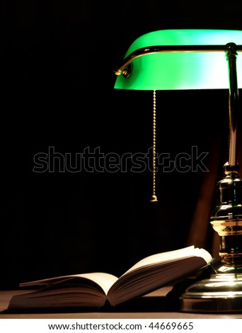 Electric green table lamp and opened book - stock photo