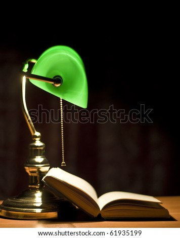 Electric green table lamp and opened book