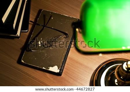 Electric green table lamp and opened book, glasses - stock photo