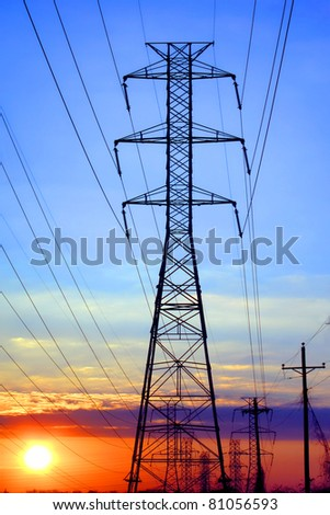 Electric grid network power high voltage transmission lines pylon tower and electrical wires at sunset - stock photo