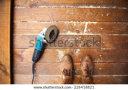 Electric grinder machine left on dusty wooden flooring with wood shavings - stock photo