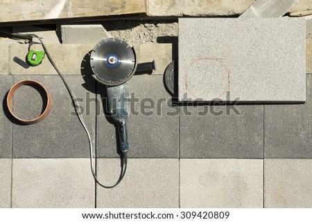 electric grinder with tiles slabs to repair  sidewalks for  construction mason  worker in the street city - stock photo