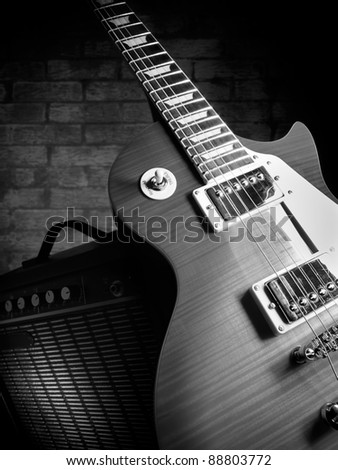 electric guitar and amplifier with brick wall in the background,closeup, for music and entertainment themes - stock photo