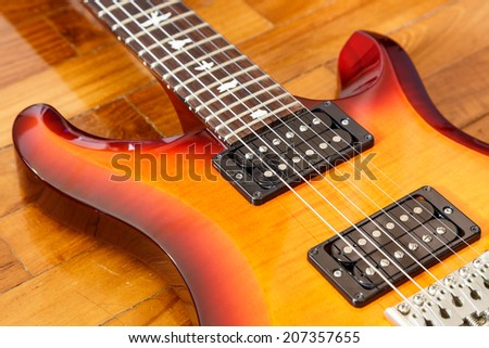 electric guitar cutwat sunburst colour on wooden floor