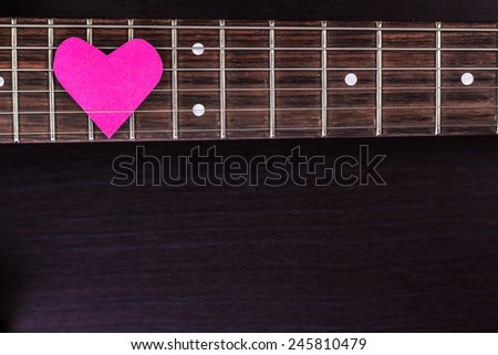 Electric guitar deck with paper heart on dark background - stock photo