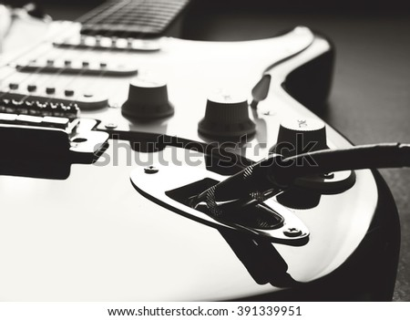 Electric guitar. Detail, focus on the cable plug. Shallow depth of field. Music, learning how to play the guitar and abstract concept