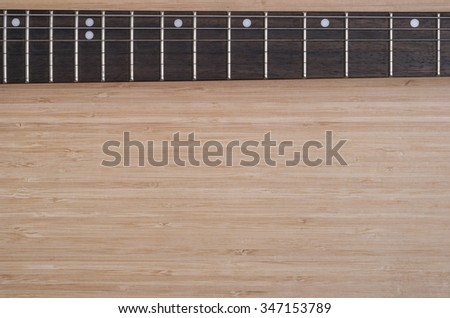 electric guitar fretboard on a wooden background texture - stock photo