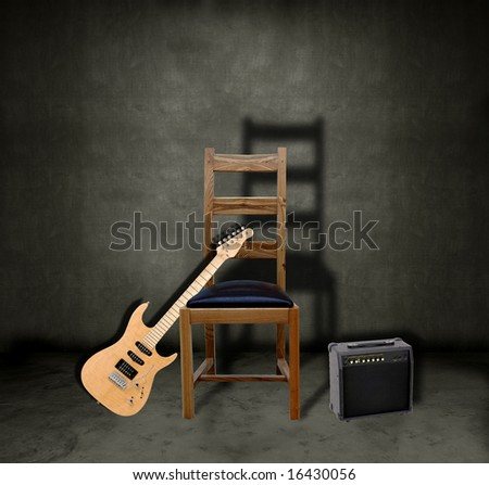 Electric guitar leaning against a chair on a dark grungy stage with an amplifier - stock photo