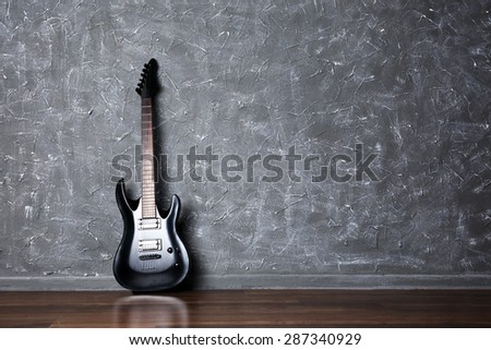 Electric guitar on gray wall background - stock photo