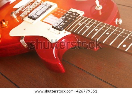 Electric guitar on wooden background, close up - stock photo