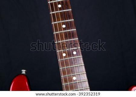 Electric guitar parts,electric guitars,strings,red guitar,guitar in studio,beautiful guitar,amazing instruments,strings guitar.guitar on black background,brown neck guitar,red guitar on black, studio - stock photo