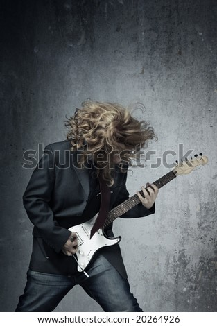 Electric guitar player on a trash background playing the rock music - stock photo