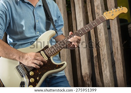 Electric guitar player, playing with old wooden background - stock photo