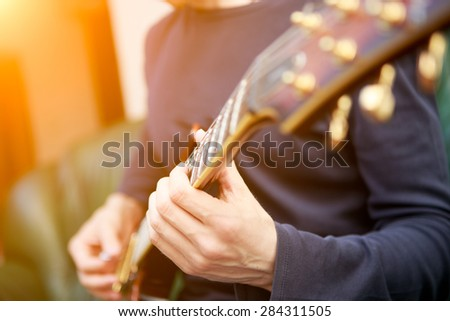 Electric guitar player. Sun lensflare - stock photo