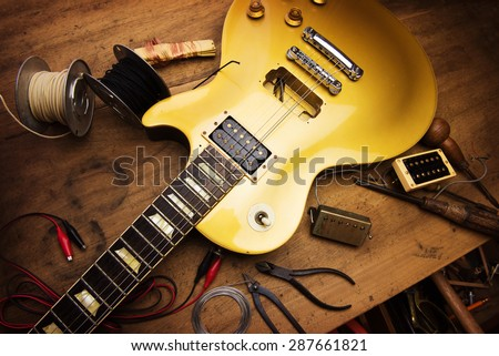 Electric guitar repair. Vintage electric guitar on a guitar repair work shop. Single cutaway solid body guitar, gold color. shallow depth of view, intentionally shot with low key shadows. - stock photo