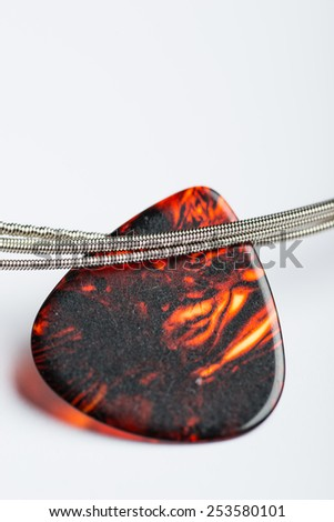 Electric guitar strings with mediator on white surface - stock photo