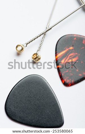 Electric guitar strings with two mediators on white surface - stock photo
